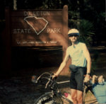 Jim-Schmid-with-bike-in-front-of-Colleton-State-Park-sign-SC-bike-tour-1986